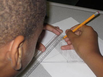 Boy drawing using a ruler.