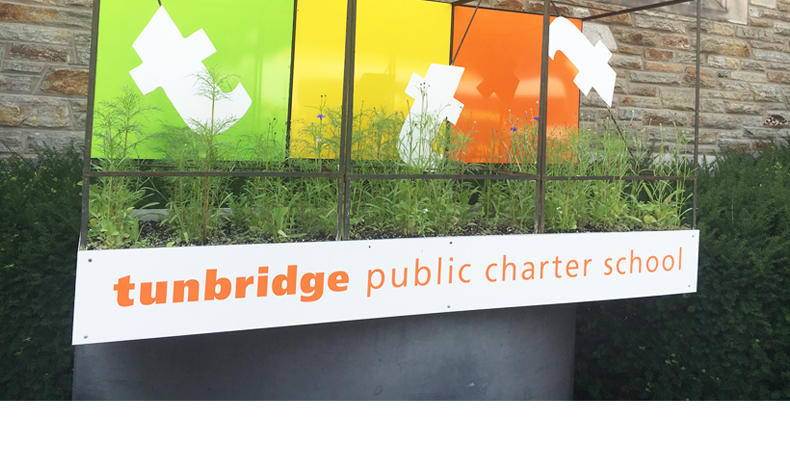 Sign for Tunbridge PCS features white Ts