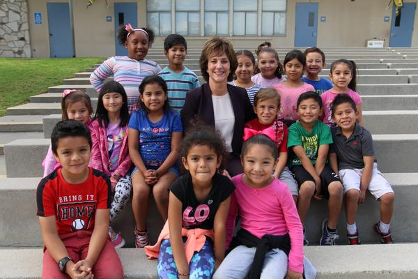 Superintendent Joanne Culverhouse surrounded by smiling students.