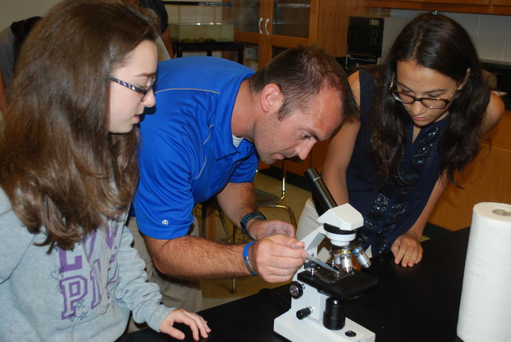 Science teacher preparing a slide on a microscope while two students observe.