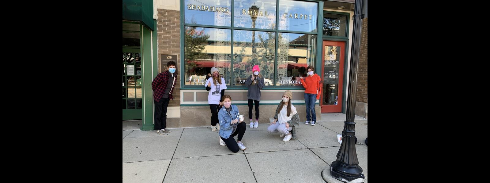 Six students socially distanced, wearing masks, in front on store window painted for homecoming