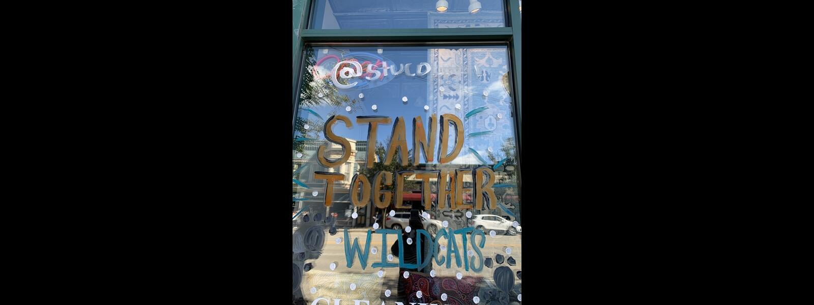 "Store window painted to say ""Stand Together"""