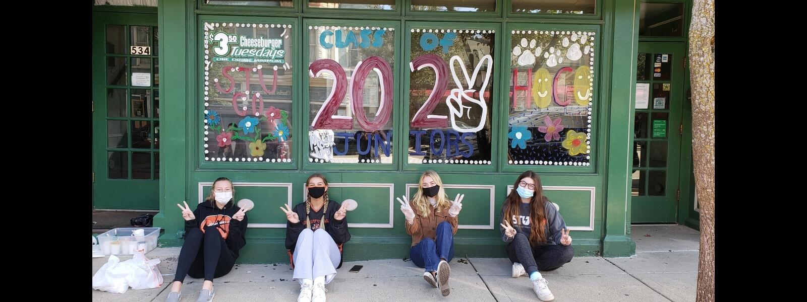 4 students sitting in front of store window they painted for homecoming