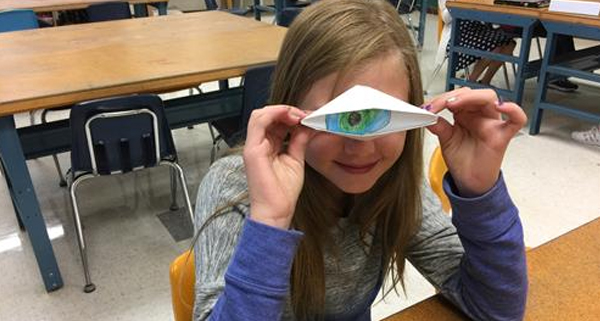 Young girl is looking through a folded piece of paper that has an eye drawn in the center.