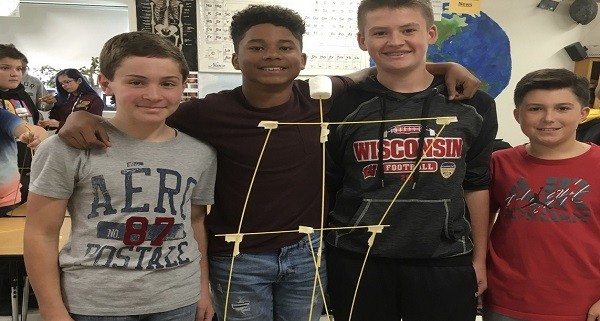 Four young boys posing in front of their marshmallow tower.