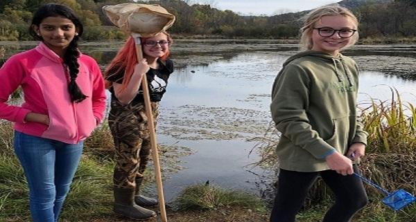 Three young girls pose outside in front of a pond while collecting samples for science research.