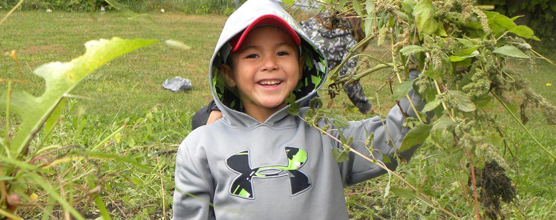 Young boy wearing a gray hooded jacket is standing next to a tree with buds; he's smiling.