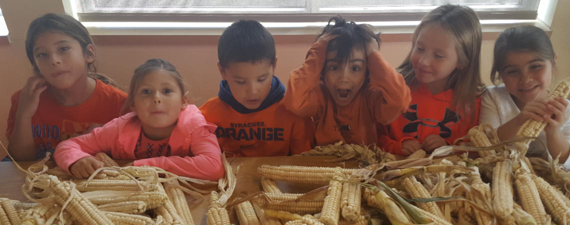 students at table with corn and making faces at the camera
