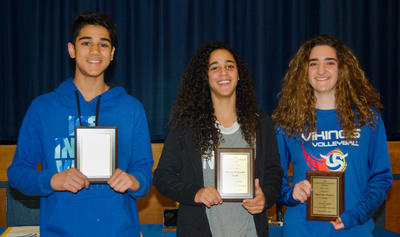 Three students holding awards
