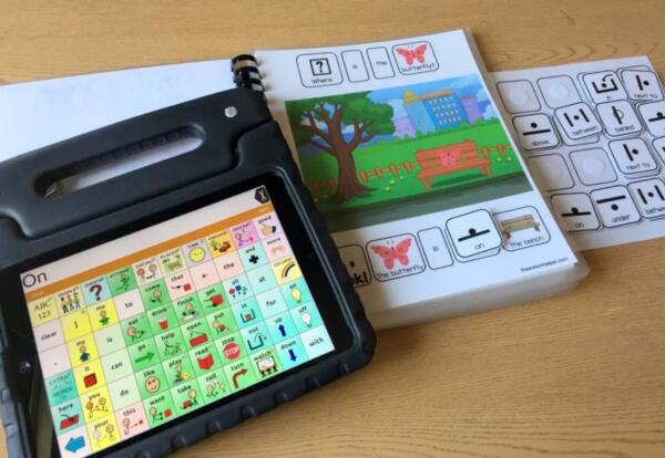 AAC unit sitting on top of an AAC workbook on a table