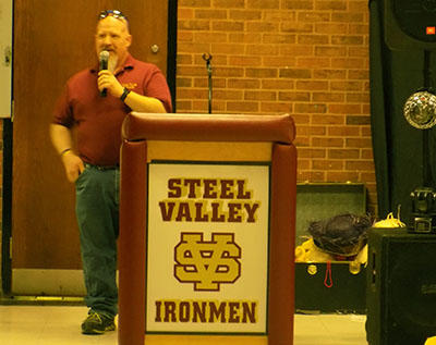 Person talking behind podium, which says Steel Valley Ironmen