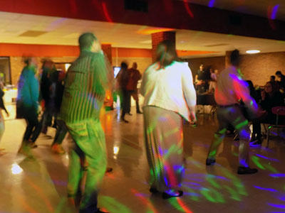 People line dancing under colored lights