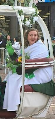 Irish Eyes is traveling in an open-air carriage, smiling and waving