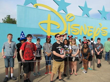 Band members posing in front of blue and yellow Disney sign