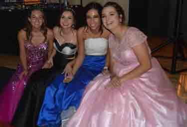Four female friends in formal dresses pose