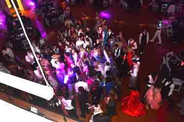 Promgoers dancing under purple lights