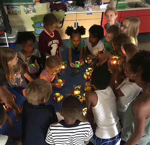 Students looking at glowing boxes they made in crafts