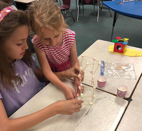 Students building tower out of mini marshmallows and toothpicks