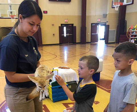 Students pet the baby fox held by a zoo staff member