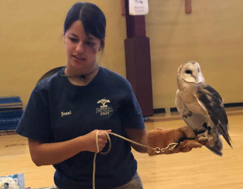 Zoo staff member holds an owl as she speaks with students