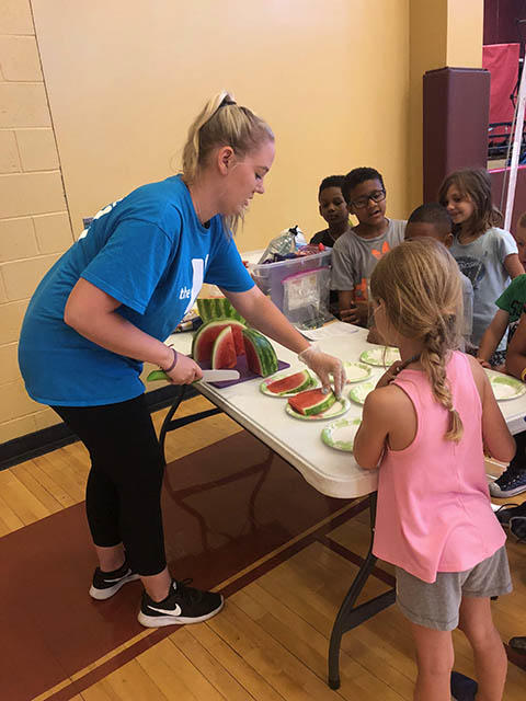 Staff member cutting watermelon for students