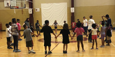 Students in circle joining hands in gym