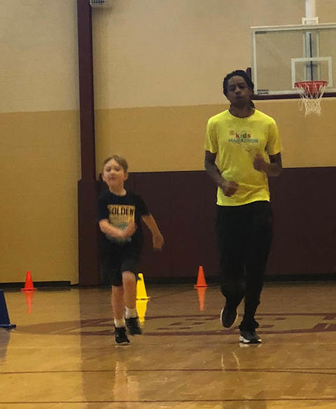 Two students running back to other side of gym