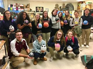 Students hold decorated finished pumpkins