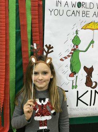 Student posing with Grinch display