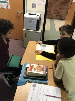 Three students discussing around a yellow folder