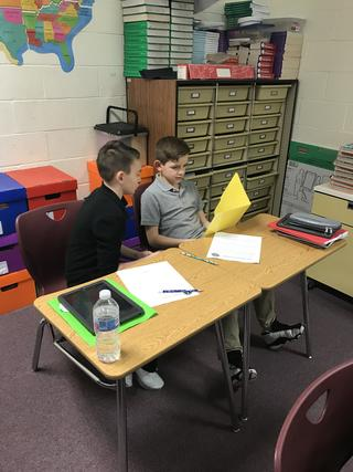 One student holds open yellow folder while both look at it