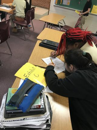 Two students work on paper next to folder marked Exhibit C