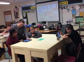 Teacher talks with students working on tablets at table