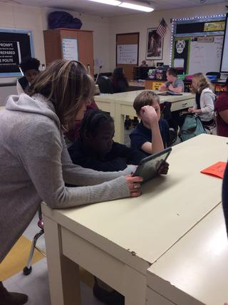 Teachers works with one student on tablet while other one looks on