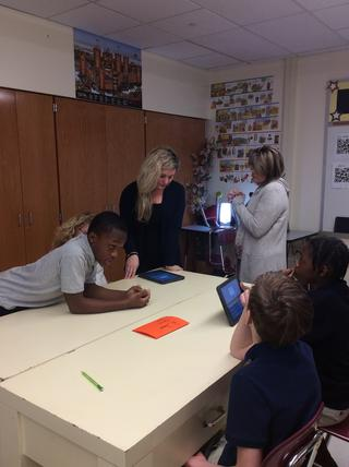 Teachers and students work with technology around a desk