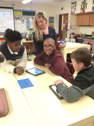 One student smiles at camera while others look at tablets on table