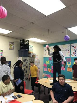 Student holds measuring stick against the ceiling