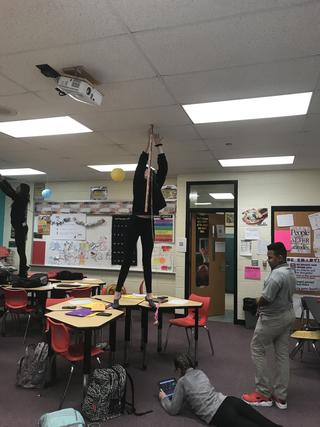 Student stands on desk and holds measuring stick to ceiling