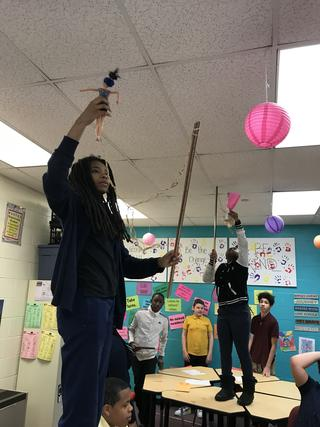 Student holds doll and measuring stick in air