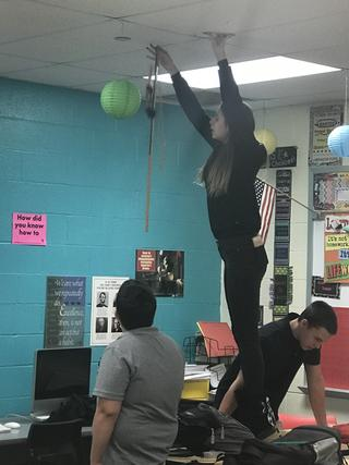 Student stands on desk and drops doll and stick