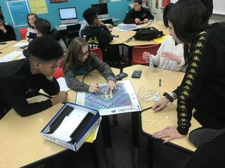 Student pointing at word on board game while others collaborate