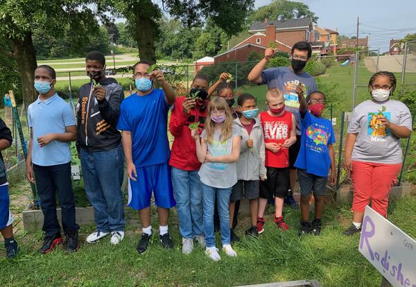 Middle school and high school students in the Extended School Year program holding radishes that they grew in the Franklin Grows Garden.
