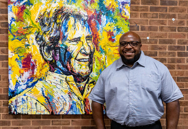 Mr. Olando Dulin stands in front of a mural of Steel Valley benefactor William V. Campbell. The mural Is colorful and Mr. Dulin is smiling.