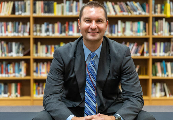 Assistant superintendent Bryan Macuga sits in front of a bookshelf in the library at Steel Valley High School.