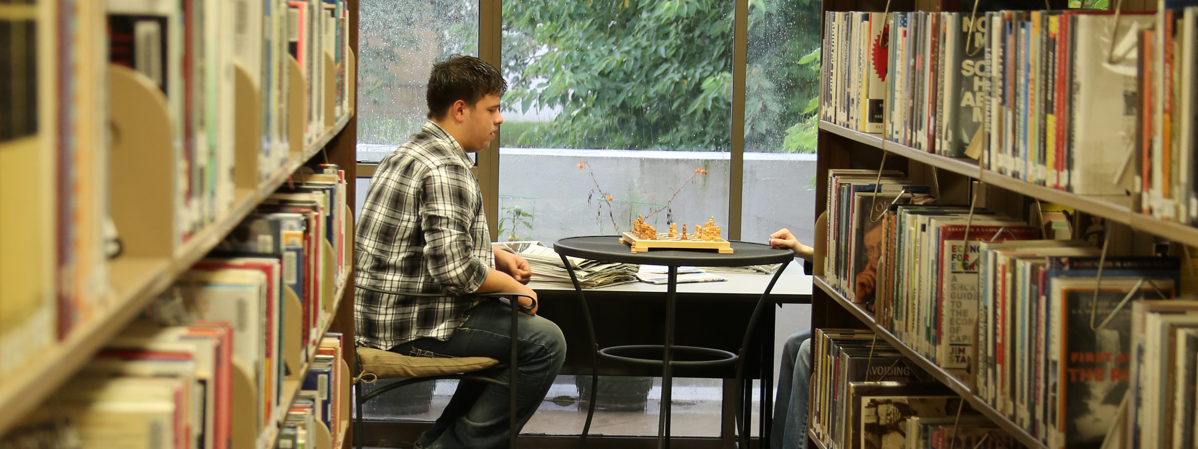 Students playing chess in the library