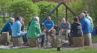 Group of people sit on stumps around a fire circle outside