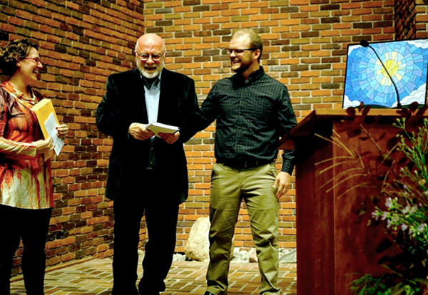 Heather L. Bunce and Ryan D. Harker, former students of Ben C. Ollenburger, Ph.D., AMBS professor of biblical theology, present him with a pre-publication copy of The Earth is the Lord's: Essays on Creation and the Bible in Honor of Ben C. Ollenburger at
