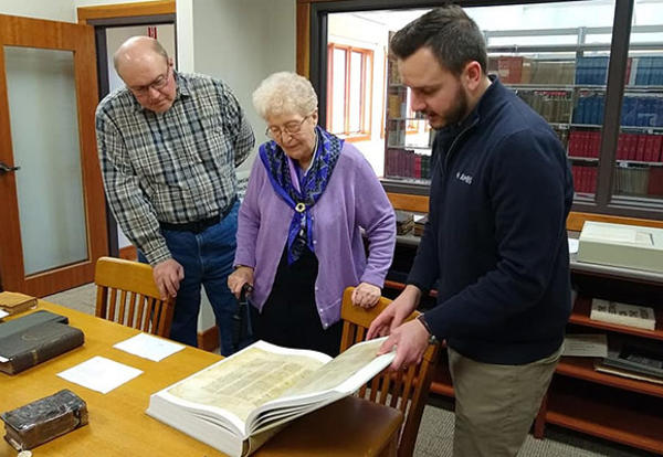 Information Services Librarian Brandon Board (at right) shows David Moser and Mary Anne Moser Codex Sinaiticus and several other items in the rare book collection. (Credit: Janeen Bertsche Johnson