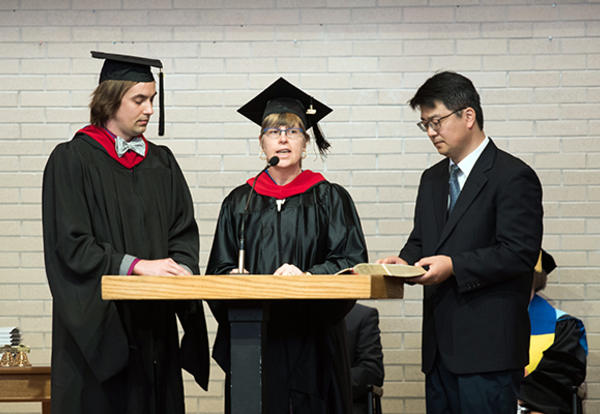 (l. to r.) Graduates Scott Litwiller of Delavan, Illinois; Margaret De Jong of Fredericton, New Brunswick, Canada; and Sungbin Kim of Seoul, South Korea, read Scripture in English, Wolof and Korean, respectively, at Anabaptist Mennonite Biblical Seminary'
