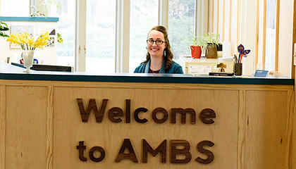 Linsey Vandrik, AMBS receptionist, at the front desk in Waltner Hall